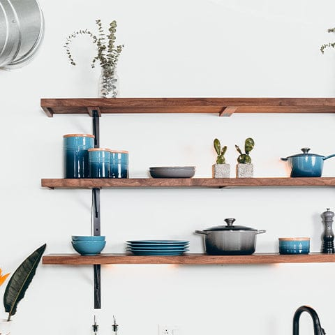3 long kitchen shelves hanging against a white wall. Each shelf has blue dishes on them with small accents of gray and green from plants.