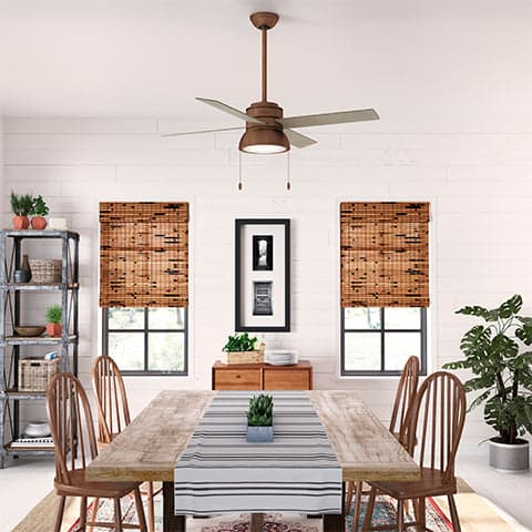 Loki fan in Weathered Copper with Barnwood blades hanging in a rustic, Bohemian space.