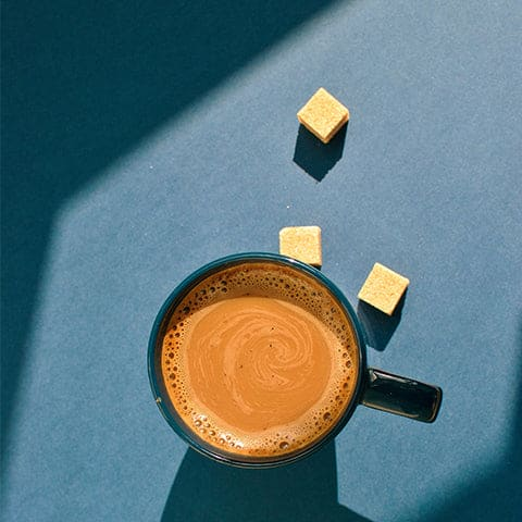 A cup of coffee sitting on a blue table with 3 cubes of sugar tossed next to it.