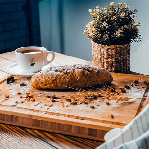 A small loaf of bread sitting on a small cutting board in front of a small plant and a small cup of coffee.