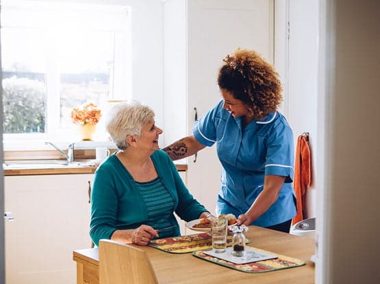 Nurse and patient discussing healthcare at a table