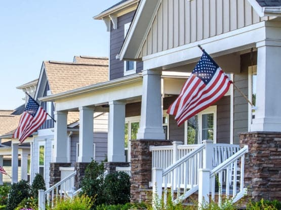 row of homes displaying the american flag to support our military