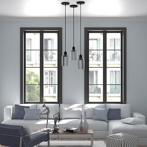Three Lochemade 1 Light Mini Pendant in Natural Iron hanging above a coffee table in a modern living room.