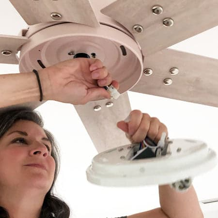 Image of a woman removing the lighting fixture from their fan.