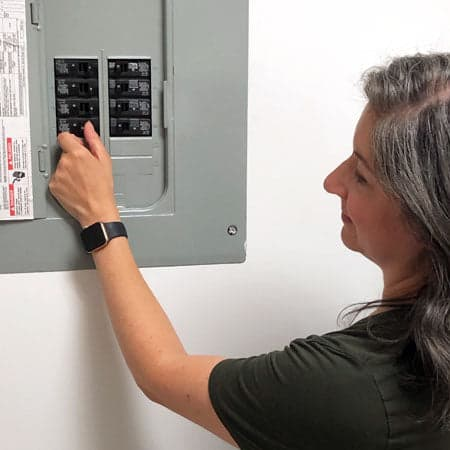 Image of a woman turning off the power using the circuit breaker before removing their ceiling fan.